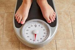Vrouwelijke naakte voeten op gewichtsschaal royalty-vrije stock afbeeldingen