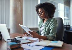 Vrouwelijke onderneemster die het bedrijfsrapport in het bureau analyseert stock foto