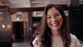 Vrouwelijke ondernemer die in bureauhal glimlachen stock videobeelden