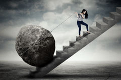 Vrouwelijke ondernemer die grote steen op de trede dragen stock fotografie