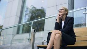 Vrouwelijke ondernemerszitting op bank, het glimlachen, die zich bij succesvolle dag verheugen stock video