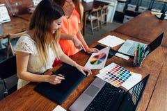 Vrouwelijke ontwerper die met cliënt bij bureau in haar bureau werken stock foto