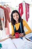 Vrouwelijke ontwerper die mobiele telefoon in bureau met behulp van royalty-vrije stock fotografie