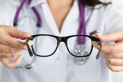 Vrouwelijke oogarts artsenhanden die paar glazen geven Goede Visie stock fotografie