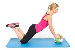 Vrouwelijke opdrukoefeningen op geneeskundebal Stock Afbeelding