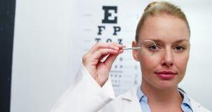 Vrouwelijke optometrist die door vergrootglas kijken stock video