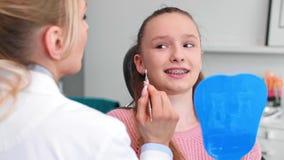 Vrouwelijke orthodontist die de tanden van het kind in het bureau van de tandarts onderzoeken stock videobeelden