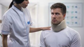 Vrouwelijke orthopedist die mannelijk geduldig het traumaresultaat bevestigen van de schuim cervicaal kraag, rehab stock videobeelden