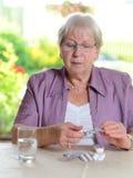 Vrouwelijke oudste met geneeskunde stock foto's