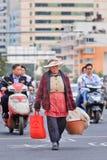 Vrouwelijke oudste met het winkelen zakken op de straat, Kunming, China Royalty-vrije Stock Foto's