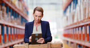 Vrouwelijke pakhuismanager die digitale tablet gebruiken stock video