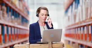 Vrouwelijke pakhuismanager die laptop met behulp van stock footage