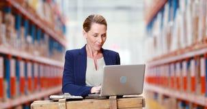 Vrouwelijke pakhuismanager die op klembord schrijven en laptop met behulp van stock footage