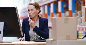 Vrouwelijke pakhuismanager gebruikend computer en sprekend op telefoon stock videobeelden