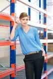 Vrouwelijke pakhuiswerknemer die zich naast planken bevinden Stock Foto's