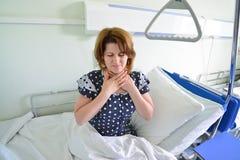 Vrouwelijke patiënt met angina op bed in het ziekenhuisafdeling stock fotografie