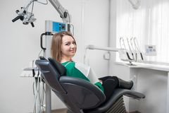 Vrouwelijke patiënt met steunen op tanden die als tandvoorzitter zitten en na behandeling bij moderne tandkliniek glimlachen stock foto's