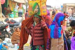 Vrouwelijke Pelgrims Dragende Bundel op Haar Hoofd op Bedevaart in India royalty-vrije stock foto
