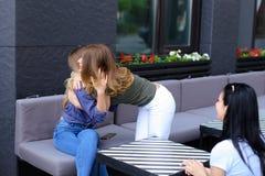 Vrouwelijke personen die bij koffie samenkomen en elkaar kussen Royalty-vrije Stock Foto