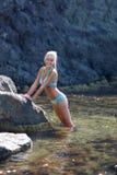 Vrouwelijke persoon die op afgezonderde plaats van wilde rotsachtige kust rusten stock afbeelding