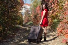 Vrouwelijke persoon die in rode kleding onder de herfstbomen lopen royalty-vrije stock afbeelding