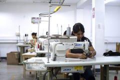Vrouwelijke Peruviaanse arbeider die met naaimachine wijzigingen maken aan kleren stock afbeelding