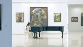 Vrouwelijke pianist die de piano in beeldgalerij spelen stock videobeelden