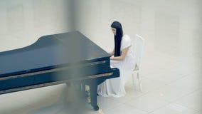 Vrouwelijke pianist die de piano in witte kleding spelen stock videobeelden