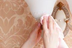 Vrouwelijke Portier Cleaning Electric Light thuis royalty-vrije stock afbeeldingen