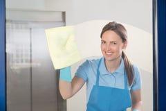 Vrouwelijke Portier Cleaning Glass royalty-vrije stock afbeelding