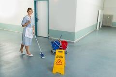 Vrouwelijke portier schoonmakende vloer stock afbeeldingen