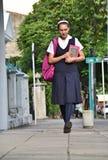 Vrouwelijke Prep Student Wearing Uniform Walking op Stoep stock afbeeldingen