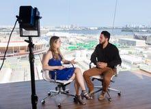 Vrouwelijke presentator die een beroemde beroemdheid vragen bij TV-studio stock afbeeldingen