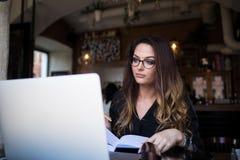 Vrouwelijke professionele op de markt brengende schrijver die een artikel voor publicatie voorbereiden die netbook gebruiken stock fotografie