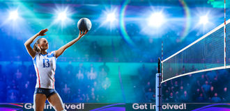 Vrouwelijke professionele volleyballspelers in actie betreffende groot hof stock afbeelding