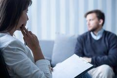 Vrouwelijke psychiater die met patiënt spreken Stock Afbeeldingen