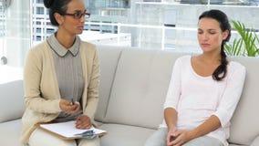 Vrouwelijke psychoanaliticus die aan gedeprimeerde vrouw spreken stock videobeelden