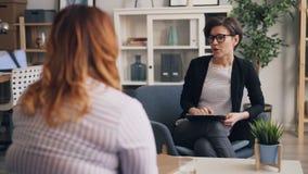 Vrouwelijke psychoanaliticus die te zware dame in bureau in kliniek raadplegen stock video
