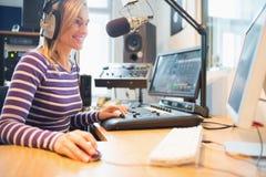 Vrouwelijke radiogastheer die computer met behulp van terwijl het uitzenden Stock Afbeelding