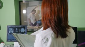 Vrouwelijke radiologiespecialist in witte laag lettende op patiënt die CT MRI procedure krijgen en medische resultaten twriting t stock videobeelden
