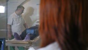 Vrouwelijke radiologiespecialist in witte laag lettende op patiënt die CT MRI procedure krijgen en medische resultaten twriting t stock video