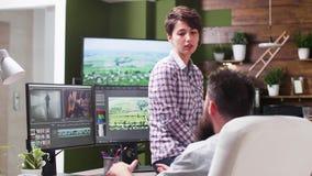 Vrouwelijke redacteursbesprekingen met mannelijke colorist in creatief agentschap stock footage