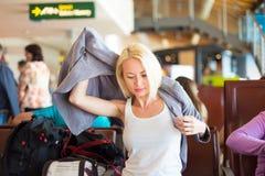 Vrouwelijke reiziger die op haar jasje zetten Stock Foto's