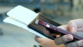 Vrouwelijke reiziger die op vertrek wachten en haar cellphone gebruiken een jong meisje schrijft een bericht Het wachten op de vl stock videobeelden