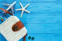 Vrouwelijke reizigerstoebehoren op blauwe achtergrond met witte rotanzak Het concept reis, vakantie, toerisme De zomer royalty-vrije stock afbeelding