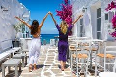 Vrouwelijke reizigersvrienden op de klassieke zomermontages van de Cycladen in Griekenland stock foto