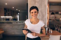 Vrouwelijke restauranteigenaar met een digitale tablet stock afbeelding
