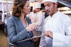 Vrouwelijke restaurantmanager die op klembord schrijven terwijl het op elkaar inwerken aan hoofdchef-kok stock afbeelding