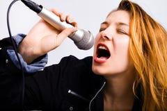 Vrouwelijke rotszanger met in hand microfoon Stock Foto's