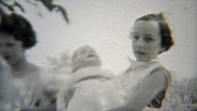 1937: Vrouwelijke schoolmakkers die poppen openluchtbinnenplaats spelen stock video